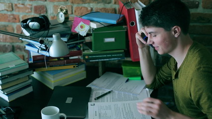 Student doing homework and chatting on cellphone at home