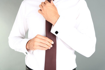 Man doing collar button up on grey background