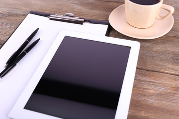 Tablet, cup of coffee, pens and folder with paper