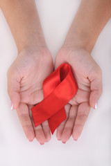 Woman with aids awareness red ribbon in hands isolated on white