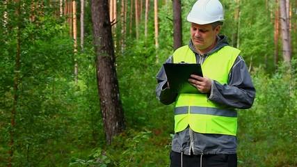Forest Officer with folder and worker behaind