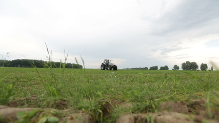 gray tractor rides on the green field on a background of forest
