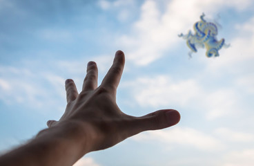 Hand reaching to the fractal figure in sky. Ffocus on hand.