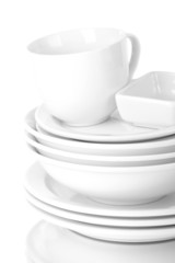 White crockery and kitchen utensils, on light background