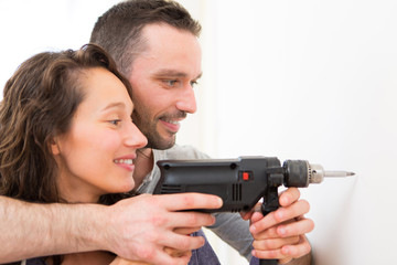 Attractive Man assisting his girlfriend using a drill