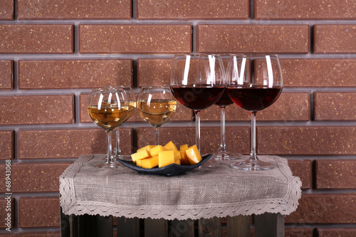Glasses of wine and cheese on box on brick wall background