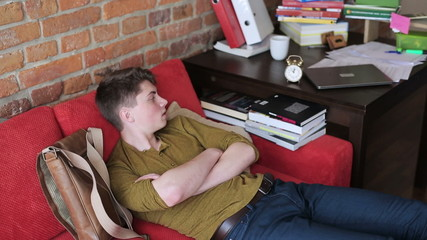Student having nap on red sofa and switching off alarm clock