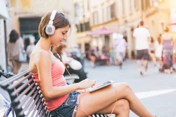 Beautiful Girl with Headphones and Digital Tablet in the City