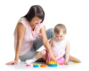 kid girl and mother play together with cup toys