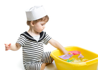 baby boy with sailor hat  playing with paper boats