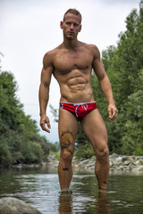 Handsome young muscle man standing in water pond, naked
