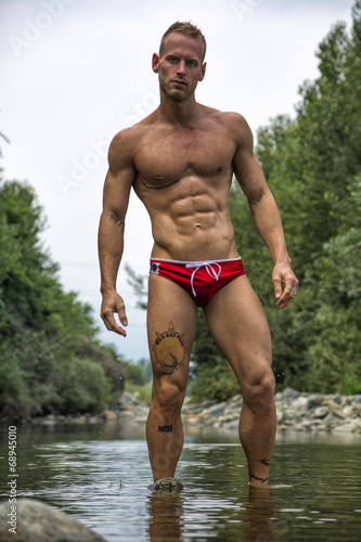 canvas print picture Handsome young muscle man standing in water pond, naked