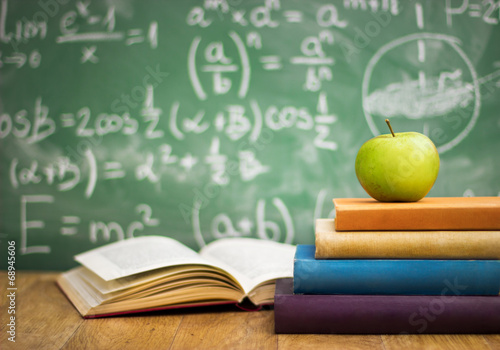 School books with apple on desk Poster