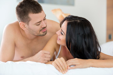 Smiling couple in bedroom