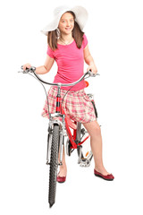 Girl with a trendy hat posing on a bike