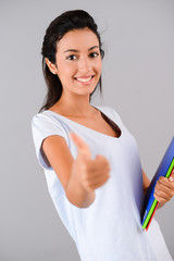 portrait of cheerful young brunette successful with thumbs up