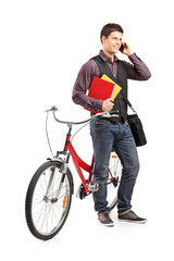Student talking on phone and standing by a bike