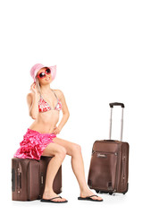 Female tourist in bikini sitting on her luggage