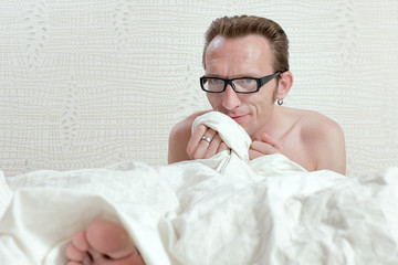 Pleased handsome naked man in bed under the white quilt sincerel
