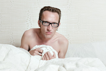 Irritated skinny naked man with angry face sitting in the bed