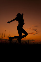 Happy woman jumping. Silhouette in the sunset sky
