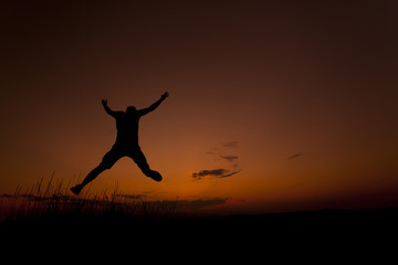 Happy man jumping. Silhouette in the sunset sky