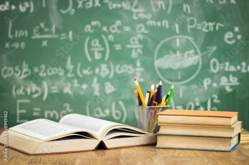 School books on desk плакат