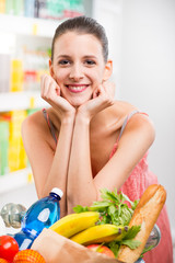 Young smiling woman shopping at supermarket with hands on chin.
