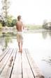 Boy walking on a dock by the lake