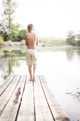 Boy walking on a dock by the lake