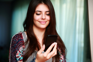 Happy woman using smartphone at home