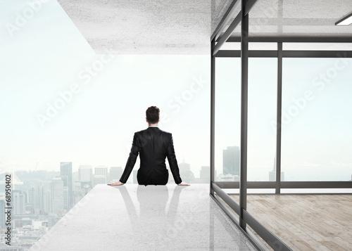 businessman sitting on skyscrapper