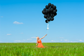 woman in orange dress lets go black balloons