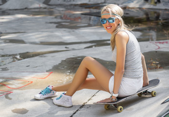 Beautiful young girl sitting on skateboard in skatepark