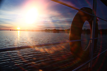 sunset on the boat lifebuoy on board