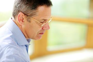 Senior man in glasses looking away