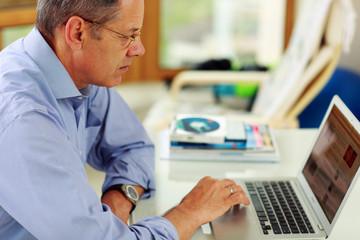 Portrait of senior caucasian man working on his laptop computer.