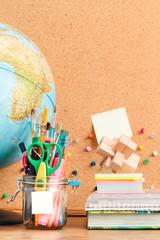 School accessories on desktop with blank pinboard in the backgro
