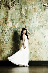 Elegant woman in evening dress on vintage background