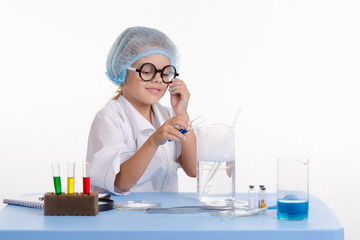 Girl pouring blue liquid in flask