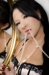 Junge asiatische Frau in Dessous mit Perlenketten