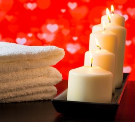 spa, white candles and towel stacked valentine day concept