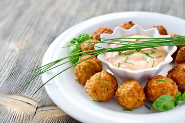Falafels on a plate with dip sauce and herbs
