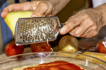 Using a grater to grate cheese