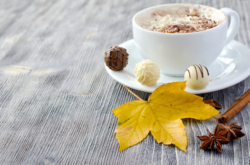 Cup of cappuccino, pralines and autumn leaves copy space