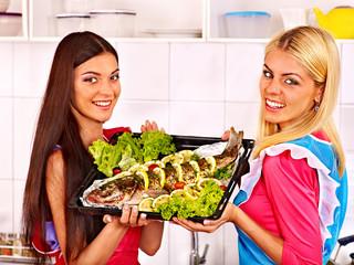 Women prepare fish in oven.