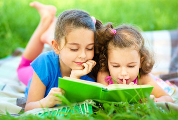 Two little girls are reading book