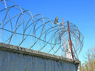 Fence with barbed wire and surveillance cameras