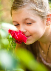 Portrait of a cute little girl smelling rose
