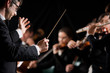 Conductor directing symphony orchestra - 68957026